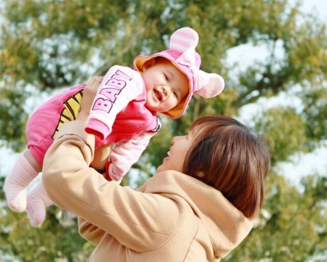 公園で抱え上げられる赤ちゃん