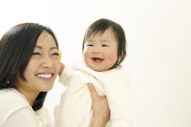 母親に抱き上げられる赤ちゃん