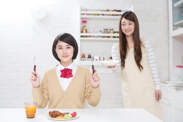 食事をする女子高生と母親