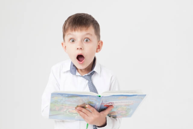本を片手に驚く少年