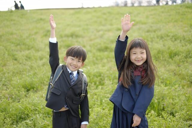 手を上げた男の子と女の子