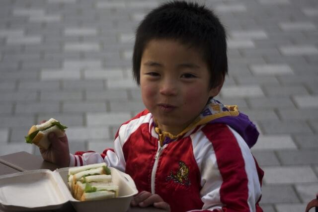 サンドイッチを食べる子供