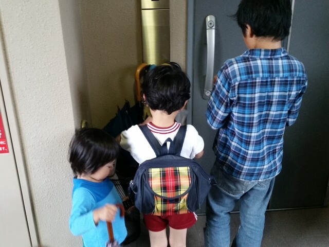 玄関の前にいる3人兄弟