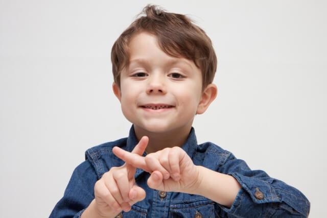 指でバツをする外国の子供