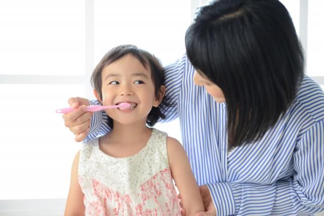 娘の歯磨きを手伝う母親