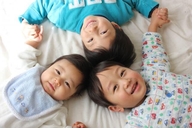 頭をくっつけて寝る3人の子供