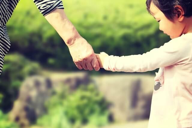 孫と手を繋ぐ祖母
