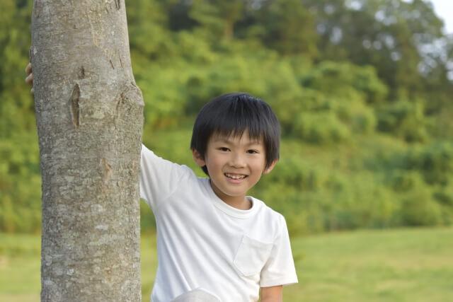 木の横に立つ子供